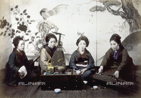 MFC-A-004626-0006 - Portrait of four japanese women in traditional dress. They are seated around a small table on which there are two teapots. Three of the four women are playing typical japanese musical instruments: the one on the left a shyamisen, at the center a biwa and on the right a koto - Data dello scatto: 1863-1868 ca. - Archivi Alinari, Firenze
