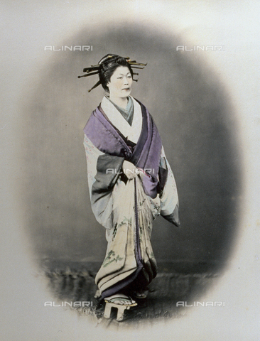 MFC-A-004626-0015 - Full-length portrait of a young japanese prostitute. She is wearing elegant traditional dress. Her hairdress is decorated with numerous lacquered sticks (kanzashi). On her feet high clogs with thongs - Data dello scatto: 1863-1868 ca. - Archivi Alinari, Firenze