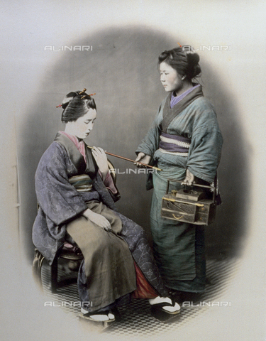 MFC-A-004626-0016 - Full-length portrait of a young japanese woman, seated. Next to her is a servant maid handing her an opium pipe, and holding an unusual iron box. They are wearing traditional clothing and wear high thonged clogs - Data dello scatto: 1863-1868 ca. - Archivi Alinari, Firenze