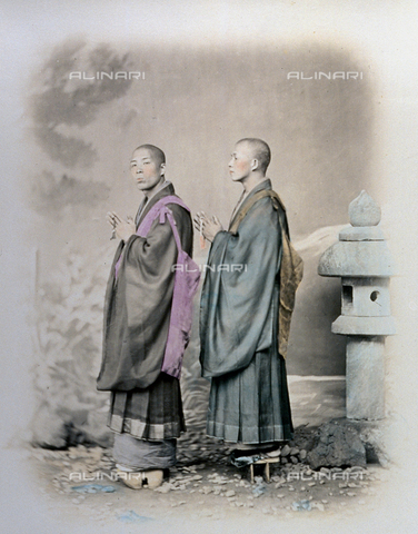 MFC-A-004626-0017 - Full-length portrait, in profile, of two japanese priests of the 'Nitchi-Re-Shu' sect. They are wearing long garments with full sleeves and high clogs. They are holding rosaries - Data dello scatto: 1863-1868 ca. - Archivi Alinari, Firenze