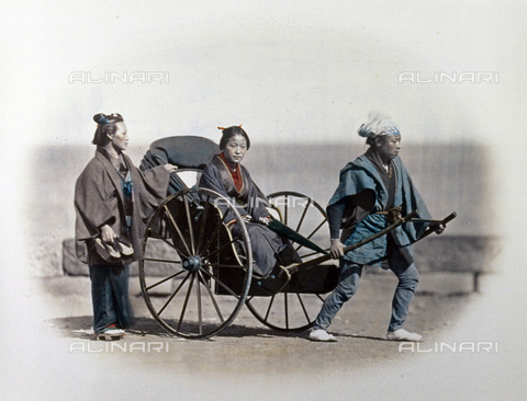 MFC-A-004626-0020 - Portrait of a young japanese woman in an elegant kimono, seated inside a rikshaw drawn by a man in humble clothing. She holds the typical japanese paper parasol in her hands. On the left, next to the rikshaw, a servant, shown full figure, holds the young lady's clogs - Date of photography: 1863-1868 ca. - Fratelli Alinari Museum Collections-Malandrini Collection, Florence