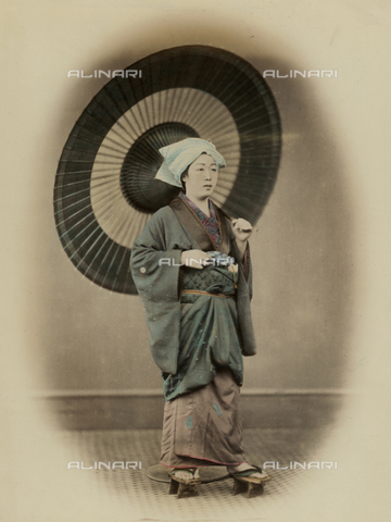 MFC-A-004626-0022 - Full-length portrait of a young japanese woman in traditional travel dress with high thonged clogs. She wears a softly draped cotton kerchief. A large paper and bamboo umbrella complete her outfit - Date of photography: 1863-1868 ca. - Fratelli Alinari Museum Collections-Malandrini Collection, Florence