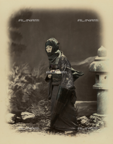 MFC-A-004626-0023 - Full-length portrait of a young japanese woman. She wears a traditional winter costume complete with a full hood on her head. In her left hand she holds an umbrella. Wooden clogs on her feet. A painted snowy landscape acts as background - Date of photography: 1865 ca. - Fratelli Alinari Museum Collections-Malandrini Collection, Florence