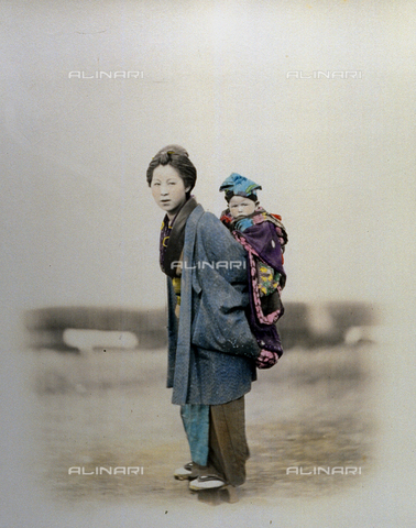 MFC-A-004626-0024 - Full-length portrait of a young japanese woman with a child. The mother, in traditional dress, carries her child on her back wrapped in a heavy colored cloth. The child's head is covered with a soft cap - Date of photography: 1863-1868 ca. - Fratelli Alinari Museum Collections-Malandrini Collection, Florence