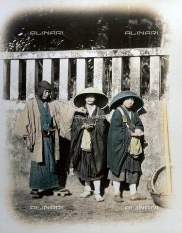 MFC-A-004626-0025 - Two mendicant japanese nuns receiving alms from a samurai dressed in traditional dress. The young nuns, shown along a road, wear humble clothing and characteristic straw hats - Date of photography: 1863-1868 ca. - Fratelli Alinari Museum Collections-Malandrini Collection, Florence