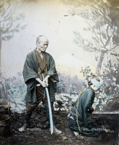 MFC-A-004626-0049 - Studio reconstruction of a japanese execution. The executioner, to the left, is holding a long katana observing the condemmed man who is kneeling, tied and bound waiting for the end. They are wearing humble traditional clothes - Data dello scatto: 1863-1868 - Archivi Alinari, Firenze