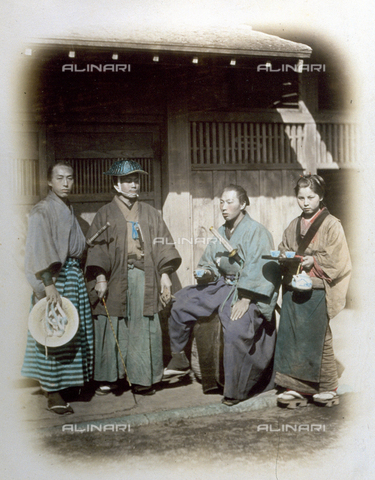 MFC-A-004626-0050 - Three members of the shogun body guards, in traditional clothes, portrayed in front of a tea house. The young soldiers, armed with long swords, are posing beside a pretty waitress who is seen serving the tea - Data dello scatto: 1865 ca. - Archivi Alinari, Firenze