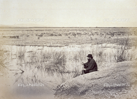 MFC-A-004631-0010 - A swamp near Grosseto. On an island, a man is seated holding a gun - Date of photography: 1863 ca. - Fratelli Alinari Museum Collections-Malandrini Collection, Florence