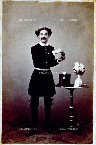 MFC-F-000373-0000 - Full-length portrait of a conjurer during a conjuring trick. A small table beside him on which there is a hat, a vase and playing cards - Date of photography: 1860-1865 ca. - Fratelli Alinari Museum Collections-Malandrini Collection, Florence