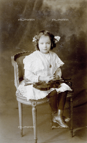 MFC-F-001194-0000 - Portrait of a little girl, seated on a chair, with a violin on her legs. She is wearing a lace dress - Date of photography: 1900-1910 ca. - Fratelli Alinari Museum Collections-Malandrini Collection, Florence
