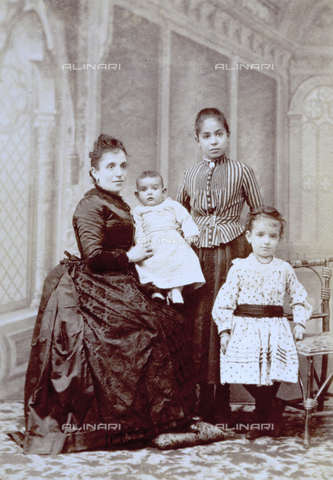 MFC-F-001527-0000 - Full-length portrait of a lady with her children. She holds her smallest one in her arms while the two bigger girls are standing next to her. They all wear elegant clothing - Data dello scatto: 1870-1880 - Archivi Alinari, Firenze