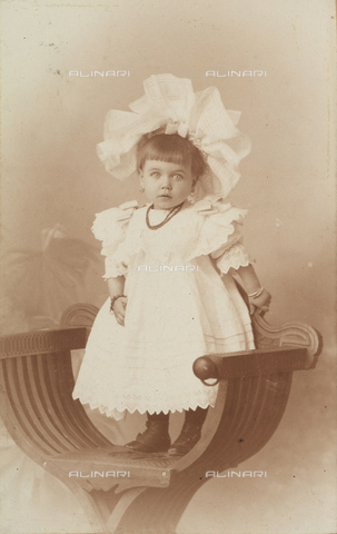 MFC-F-001542-0000 - Portrait of a little girl in an elegant dress and with a striking hat. She is standing on a chair - Data dello scatto: 1890-1900 ca. - Archivi Alinari, Firenze