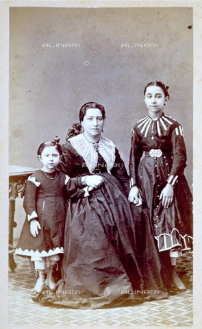 MFC-F-001619-0000 - Full-length portrait of a woman with children. She is seated in the middle and holds the two little girls by the hands. They wear elegant clothing - Data dello scatto: 1860-1870 ca. - Archivi Alinari, Firenze