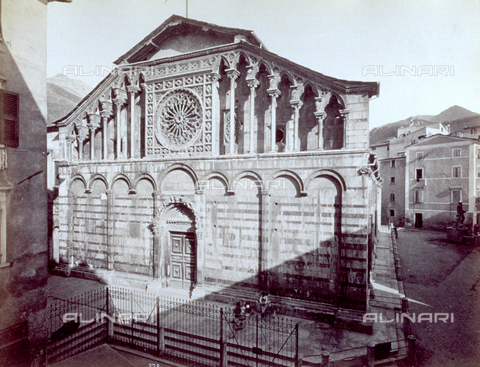 MFC-F-001654-0000 - Facade of the romanesque-gothic Cathedral of Carrara, with the contiguous plain and the fountain with the statue by Andrea Doria. An open umbrella is hung on the railing - Data dello scatto: 1870-1890 ca. - Archivi Alinari, Firenze