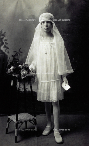 MFC-F-001692-0000 - Portrait of a young adolescent, standing, on her First Communion Day. She is wearing a white veil and leaning against a tripod on which there are a few roses - Date of photography: 31/05/1925 - Fratelli Alinari Museum Collections-Malandrini Collection, Florence