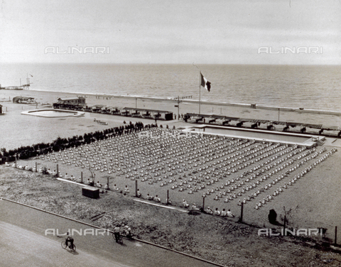 MFC-F-001723-0000 - Marine summer camp. The students, lined up on the beach, are doing gym exercises. In the background the bathing establishment and the sea - Date of photography: 1930 ca. - Fratelli Alinari Museum Collections-Malandrini Collection, Florence