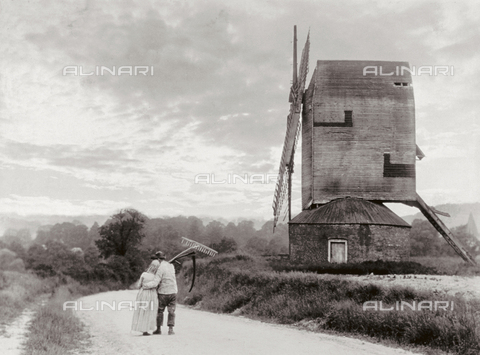 MFC-F-001885-0000 - A couple of peasants arm in arm moving down a country path. A windmill can be seen on the right