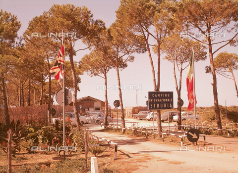 MFC-F-003629-0000 - Entrance to the 'Camping Internazionale Etruria', in a pine grove in Castiglione della Pescaia. A few cars are parked in front of the entrance. In the foreground two flagspoles with the english and italian flags - Date of photography: 1955-1965 ca. - Fratelli Alinari Museum Collections-Malandrini Collection, Florence