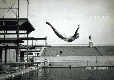 MFC-F-003927-0000 - Diver diving into a pool. On the left of the picture, the diving board. In the background the terraces