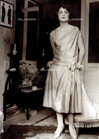 MFC-F-004045-0000 - Ritratto, a figura intera, di giovane signora in abito da sera, stile charleston. L'effigiata posa nel soggiorno di un'abitazione e si appoggia ad una poltroncina - Data dello scatto: 1925-1930 ca. - Archivi Alinari, Firenze