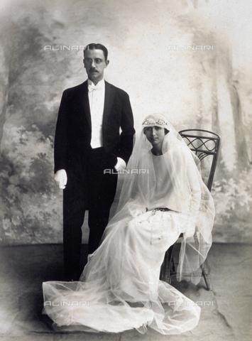 MFC-F-004235-0000 - Coppia di giovani sposi ritratti nel giorno delle nozze. La donna posa seduta, avvolta nel lungo velo nuziale - Data dello scatto: 1920-1930 ca. - Archivi Alinari, Firenze