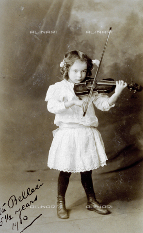 MFC-F-004255-0000 - Full-length portrait of a little girl playing the violin. She is wearing a light colored lace dress - Date of photography: 1910 - Fratelli Alinari Museum Collections-Malandrini Collection, Florence