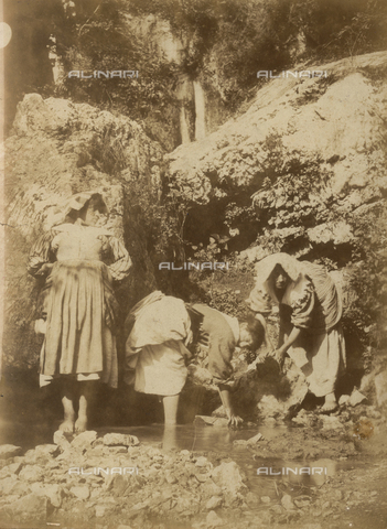 MFC-S-000927-0005 - Full-length portrait of three peasants in ciociarian dress. Two women are washing clothes in a brook. The third is standing, leaning against a rock. In the background a waterfall - Data dello scatto: 1870 ca. - Archivi Alinari, Firenze