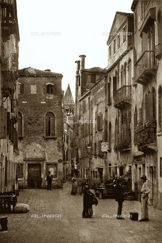MFC-S-001456-0035 - View of the Salizzada San Samuele in Venice, with passersby. On the right a fruitvender and further back the sign of a municipal school. In the background a lane