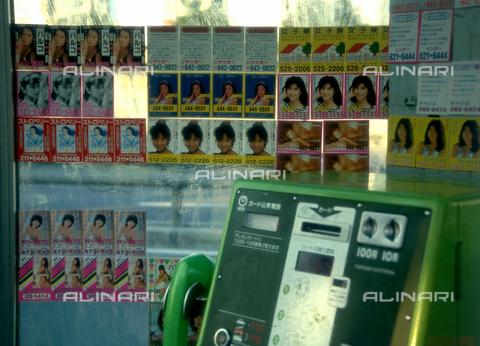 MFV-F-TK0159-0000 - Biglietti con foto e numeri di telefono di ragazze, interno di una cabina telefonica di Tokyo - Data dello scatto: 1977 - Fosco Maraini/Proprietà Gabinetto Vieusseux©Fratelli Alinari