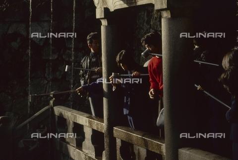"""MFV-S-JPN369-0091 - Visitatori bevono l'acqua della cascata all'interno del Tempio di Kiyomizu-dera (""""Il tempio dell'acqua pura""""), Kyoto - Data dello scatto: 11/1987 - Fosco Maraini/Proprietà Gabinetto Vieusseux©Fratelli Alinari"""
