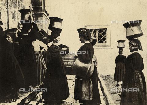 MLD-F-000086-0000 - Giovani donne di Scanno ritratte alla fonte. Le effigiate vestono abiti tradizionali e trasportano i recipienti dell'acqua sulla testa con l'apposito copricapo - Data dello scatto: 1900-1920 ca. - Archivi Alinari, Firenze