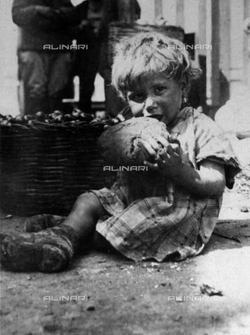 MLD-F-000116-0000 - Ritratto di bambina. La bimba, sporca e malvestita, è ritratta seduta per terra mentre sta mangiando un grosso pezzo di pane - Data dello scatto: 1910-1920 ca. - Archivi Alinari, Firenze