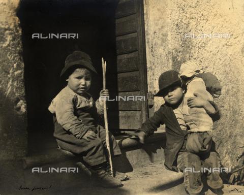MLD-F-000147-0000 - Ritratto di due bimbi vestiti di stracci, seduti sull'uscio di un edificio rurale. Uno dei bambini ha in braccio il fratellino di pochi mesi; l'altro tiene in mano un bastone - Data dello scatto: 1910-1920 ca. - Archivi Alinari, Firenze