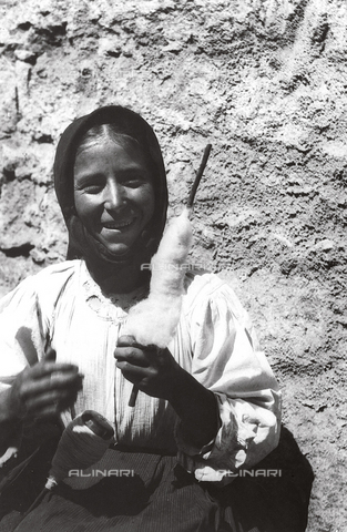 MLD-F-000180-0000 - Half-length portrait of a young woman. She is smiling and showing her spindle and the staff on which the thread is wound - Data dello scatto: 1900-1920 ca. - Archivi Alinari, Firenze