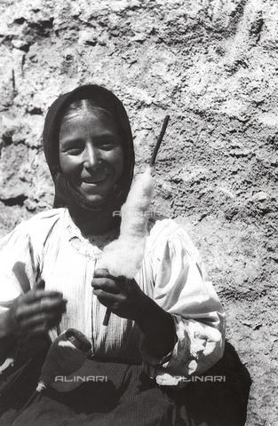 MLD-F-000180-0000 - Ritratto a mezzo busto di giovane donna. L'effigiata mostra sorridente il fuso per la filatura e il bastoncino su cui è arrotolato il cotone - Data dello scatto: 1900-1920 ca. - Archivi Alinari, Firenze