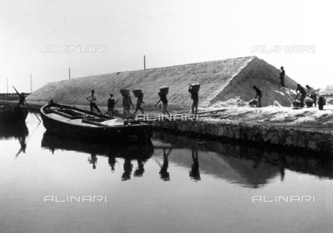 MLD-F-000182-0000 - Alcuni operai di una salina siciliana sono ritratti mentre trasportano ceste di sale dal deposito ad una chiatta - Data dello scatto: 1900-1920 ca. - Archivi Alinari, Firenze