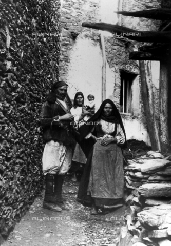 MLD-F-000202-0000 - Full-length portrait of a couple of elderly in Sardinian traditional costumes. Behind them is a young woman with her small son - Data dello scatto: 1900-1920 ca. - Archivi Alinari, Firenze