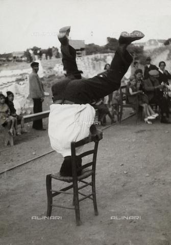 MLD-F-000586-0000 - Giovane greco in una posa del folkloristico ballo con le sedie, a Laurion - Data dello scatto: 1940-1950 ca. - Archivi Alinari, Firenze