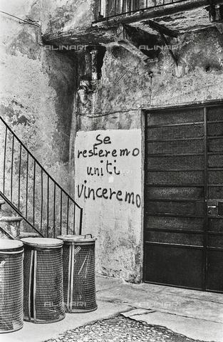 """NPA-F-000013-0000 - """"Milano Hinterland 1950-1970"""": muro di una casa con la scritta """"se resteremo uniti vinceremo"""" - Data dello scatto: 1960 - Archivi Alinari, Firenze"""
