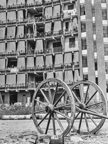 """NPA-F-000020-0000 - """"Milano Hinterland 1950-1970"""": ruote di carro davanti a un grattacielo di Via Crescenzago - Data dello scatto: 1968 - Archivi Alinari, Firenze"""