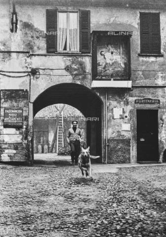 """NPA-F-000070-0000 - """"Terre di periferia"""": un uomo con il cane lungo il Naviglio Grande - Data dello scatto: 1960 - Archivi Alinari, Firenze"""