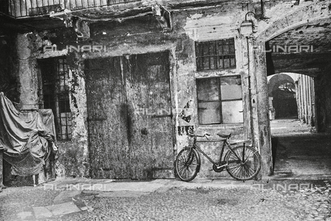 """NPA-F-000071-0000 - """"Testimonianze ambientali. 1970"""": bicicletta appoggiata al muro di una casa lungo il Naviglio Grande - Data dello scatto: 1970 - Archivi Alinari, Firenze"""