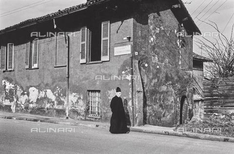 """NPA-F-000078-0000 - """"Terre di periferia"""" - """"Mi. Andà de pret"""": un prete in una strada della periferia di Milano lungo il Naviglio Grande - Data dello scatto: 1960-1970 - Archivi Alinari, Firenze"""