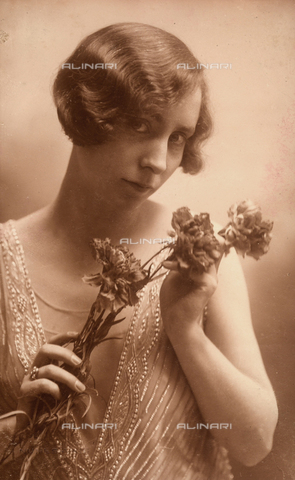 NVM-F-000224-0000 - Half-bust portrait of a young woman holding a bunch of carnations and wearings a low-necked, beaded dress