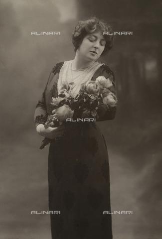 NVM-F-000400-0000 - Ritratto della cantante lirica Toti Dal Monte, mentre posa lo sguardo su un fascio di rose che tiene tra le braccia. Indossa un abito in velluto devoré a motivi floreali. - Data dello scatto: 1925 - 1930 - Archivi Alinari, Firenze