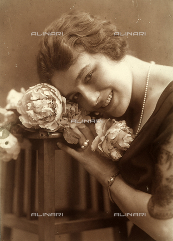 NVM-F-000461-0000 - Half-bust portrait of a smiling young woman, holding a bouquet of peonies near her face. On the low-cut neckilne of her dress, lies a long strand of pearls