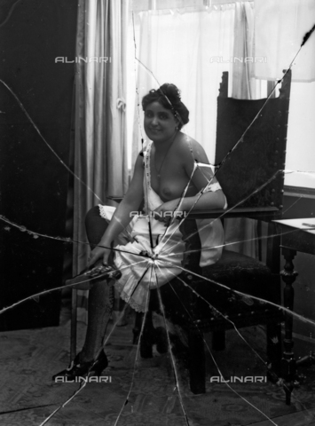 NVM-F-003183-0000 - Full-length portrait of a woman in skimpy clothes on a chair - Date of photography: 1900-1910 - Fratelli Alinari Museum Collections-Nunes Vais Archives, Florence