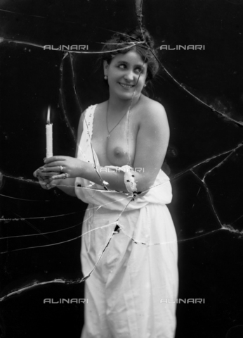NVM-F-003208-0000 - Female Portrait  in skimpy clothes with candle - Date of photography: 1900-1910 - Fratelli Alinari Museum Collections-Nunes Vais Archives, Florence