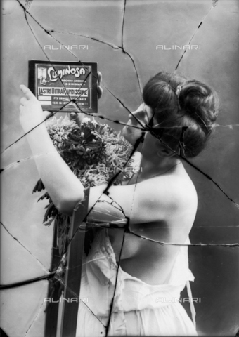 "NVM-F-003214-0000 - Female Portrait  in skimpy clothes. The woman shows an advertisement of Società Anonima ""La Luminosa"" for  plates high speed - Date of photography: 1900-1910 - Fratelli Alinari Museum Collections-Nunes Vais Archives, Florence"