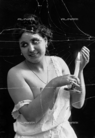 NVM-F-003247-0000 - Female Portrait  in skimpy clothes with candle - Date of photography: 1900-1910 - Fratelli Alinari Museum Collections-Nunes Vais Archives, Florence